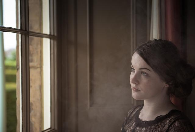 Žena s hnedými vlasmi pozerá cez sklenené dvere do záhrady.jpg