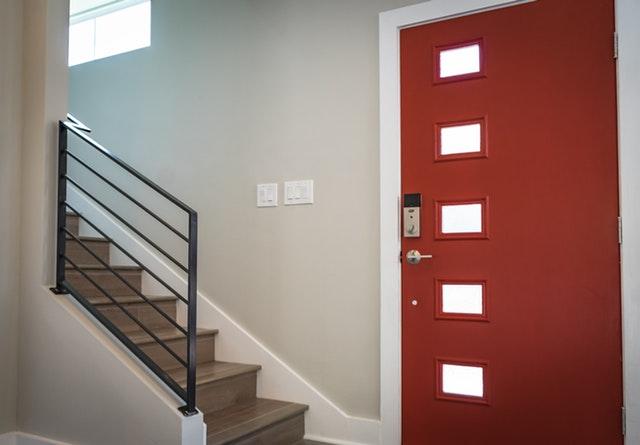 Vchodové dvere, vedľa ktorý je schodisko so zábradlím.jpg