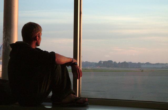 Mladý muž pozerá cez okno, veľké sklá